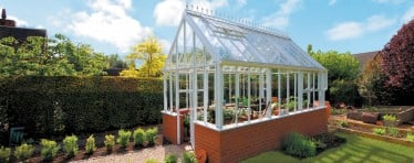 A White Hartley Botanic Greenhouse With A Brick Base