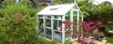 White Hartley Botanic Glass to Ground Greenhouse in a Garden
