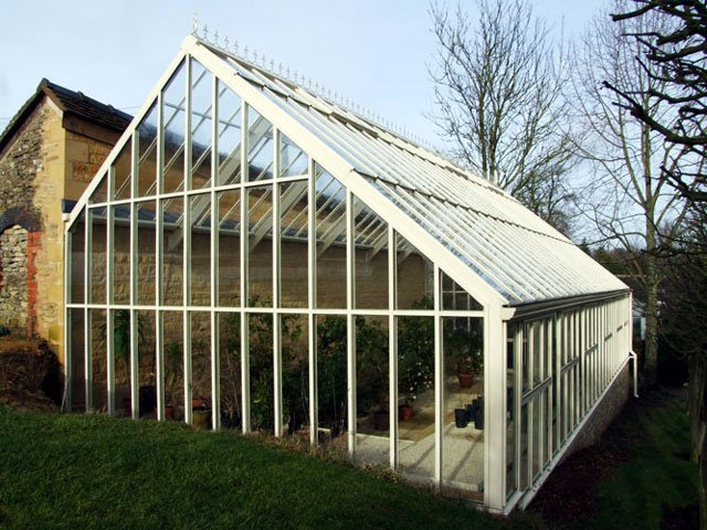 A three quarter span Hartley Lean-to glasshouse build against a stone wall.